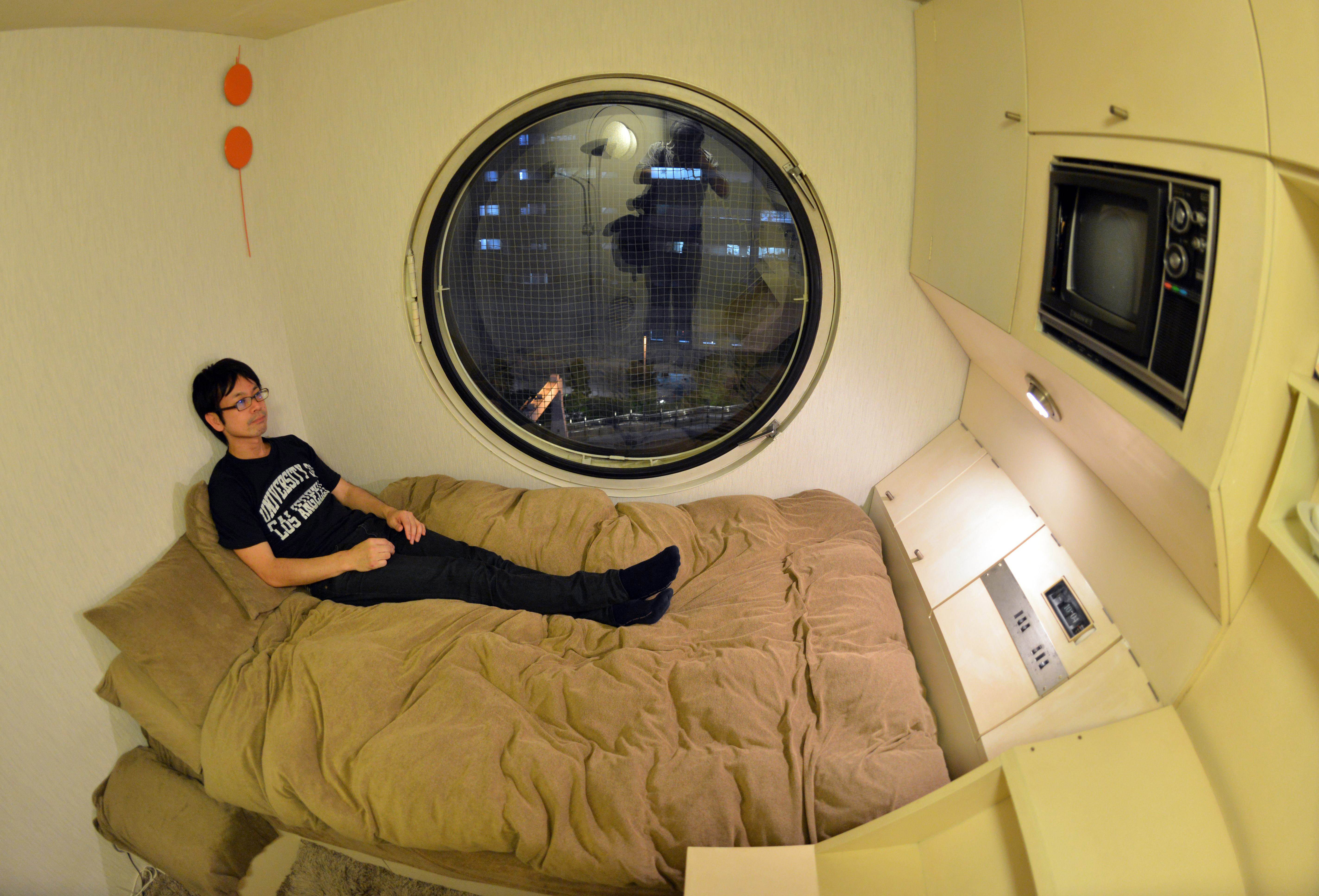 TO GO WITH STORY Japan-architecture-capsule-Nakagin,FEATURE by Katie Forster This picture taken on September 9, 2014 shows a resident of the Nakagin Capsule Tower Masato Abe at his room in Tokyo. The 140 units at Nakagin represent a special part of the history of architecture and one that is worth protecting against plans to tear it down. Around half of the capsules, designed by Japanese architect Kisho Kurokawa in 1972, are currently in use as offices, art studios and second homes, but 20 of the tiny spaces are full-time homes.   AFP PHOTO / Yoshikazu TSUNO