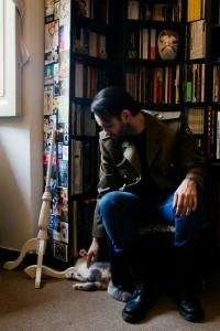 Albert che accarezza una gatta sperando che non gli distrugga la libreria