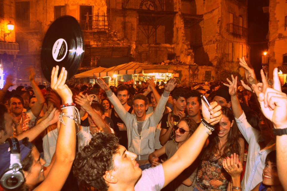 In basso a sinistra Paquita (con tanto di ragazzo che si fa un selfie insieme a lei) tutto intorno la gente del mercato di Vucciria a Palermo