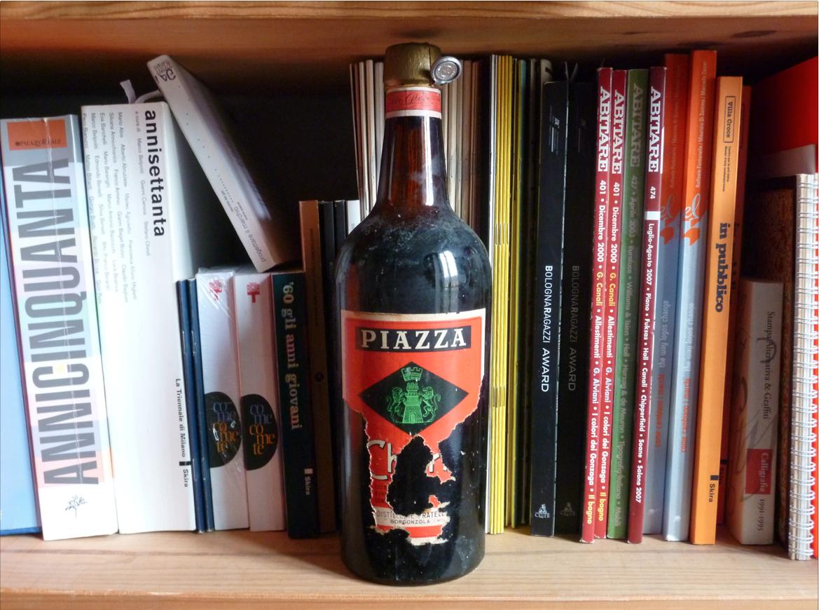 Una bottiglia Piazza e alle spalle alcuni libri scritti e impaginati da Mario